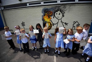 Schoo children show off their drawings of a mural, attributed to the graffiti artist Banksy, painted on the outside of a classroom at Bridge Farm primary school in Bristol