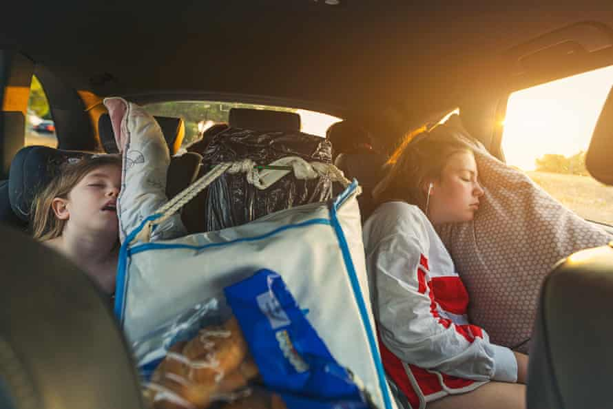 Two sisters asleep on roadtripGettyImages-1015400126