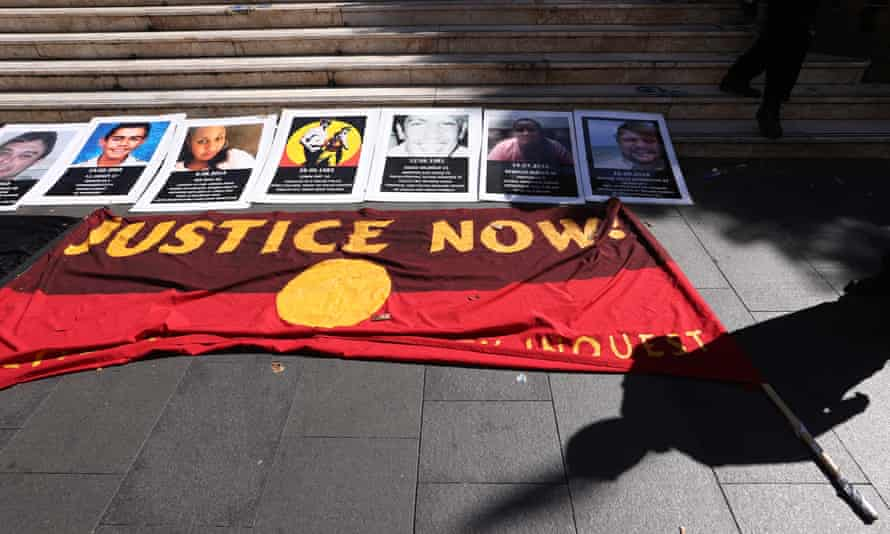 """An Aboriginal flag with """"Justice Now"""" written on it lies on the pavement before a protest march on 10 April 2021 in Sydney, Australia."""