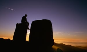 Man sitting on rocks at sunset
