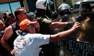 Municipal workers scuffle with police, as they protest against layoffs in Athens.