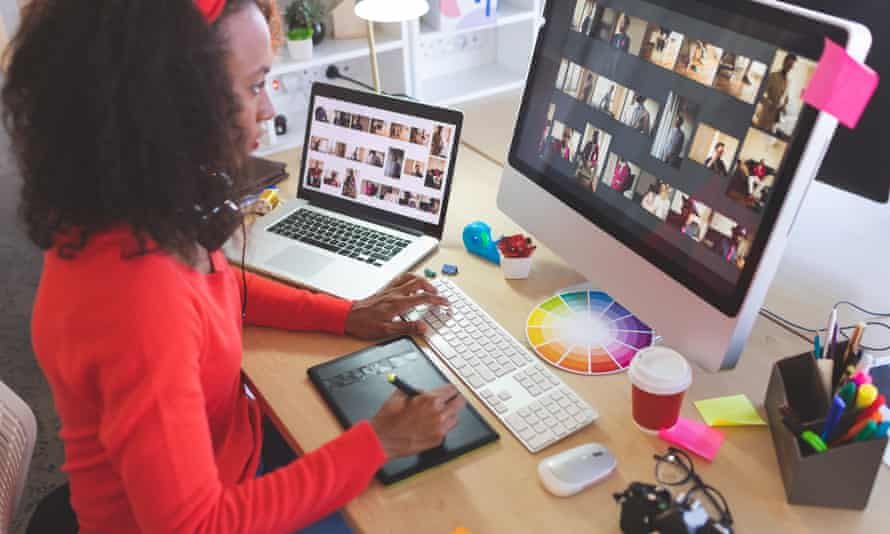 Female graphic designer using graphic tablet at deskSide view of young mixed-race female graphic designer using graphic tablet at desk in a modern office
