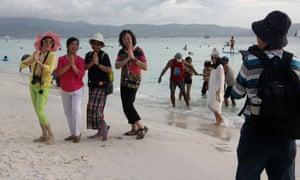 Tourists pose for photos on a beach on Boracay Island in January.