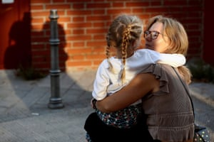 A girl is held by her mother as she arrives for her first day of school in Madrid, Spain