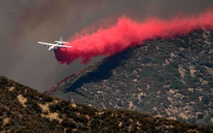 A firefighting airplane makes a low-flying retardant drop on a ridge