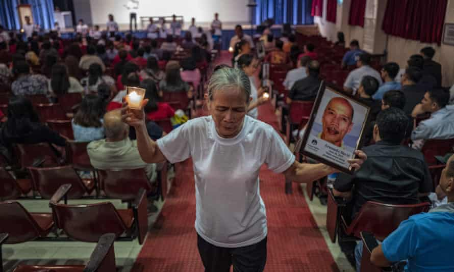 A woman, whose relative was killed in the drug war, shows a picture of her loved one to the audience