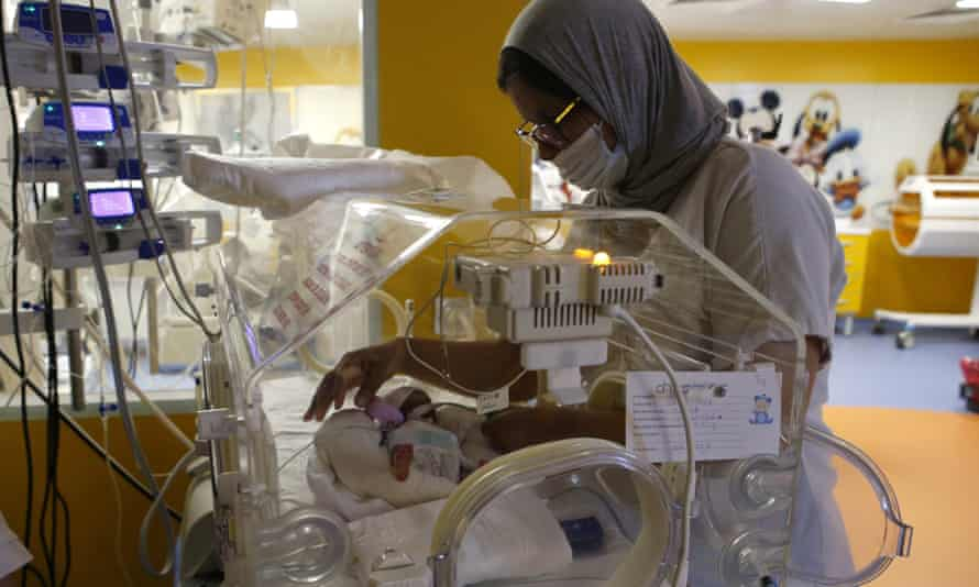 A Moroccan nurse takes care of one of the nine babies protected in an incubator.