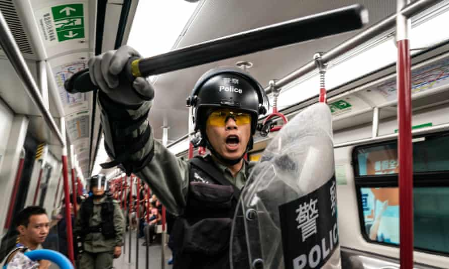 Riot police enter a train at the Tung Chung MTR station after protesters block the transport routes to Hong Kong International Airport.