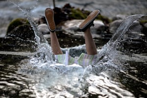 A participant jumps into the 6c water of the Grundlseer Traun river wearing a Dirndl dress.