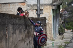 Military police officer Everaldo Pinto, dressed as superhero Captain America, greets children amid the Covid-19 pandemic in Petropolis