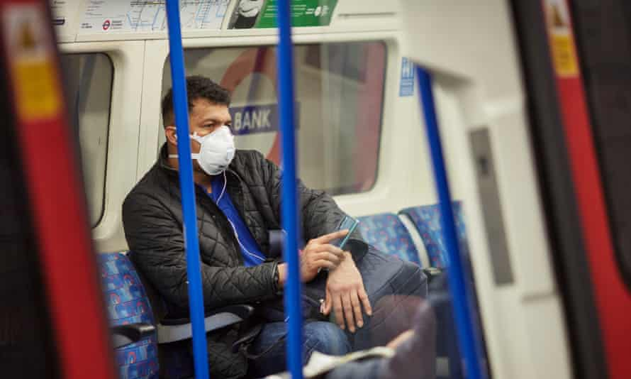 a man travels on the tube with a face mask