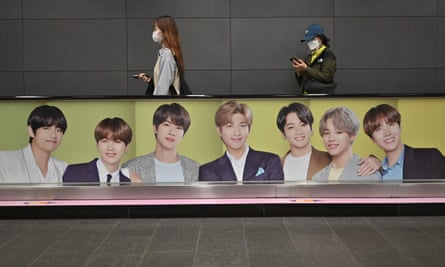 People walk past a commercial poster showing K-pop group BTS
