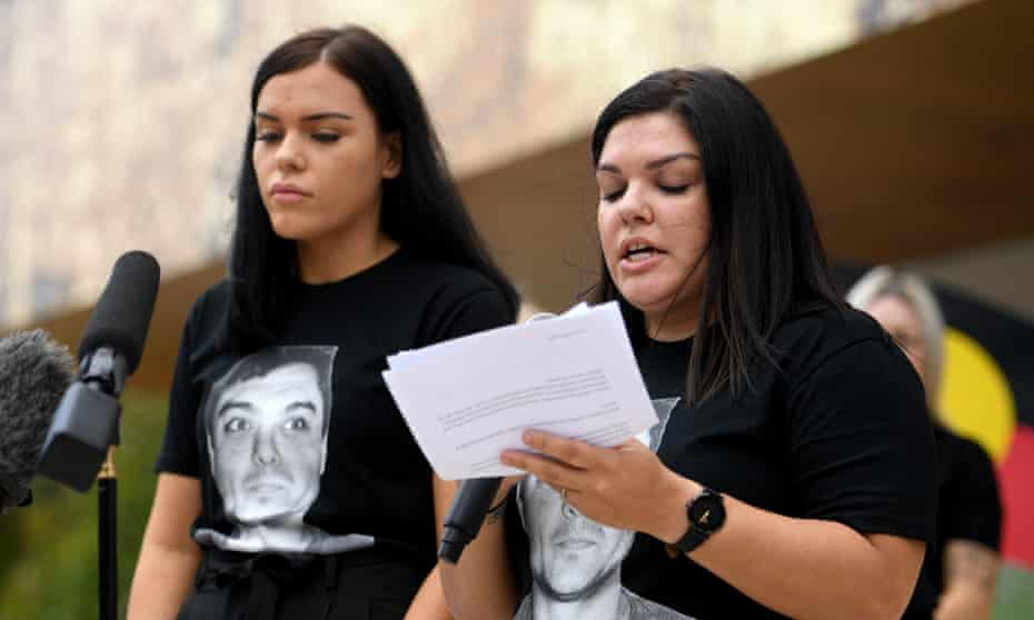 Makayla Reynolds, left, and her sister Taleah read a statement to media as family watch on after the inquest into the death in custody of Nathan Reynolds.