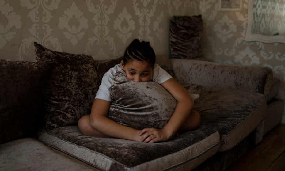 Ava, aged eight, sits on her sofa looking sad and resting her head on a cushion