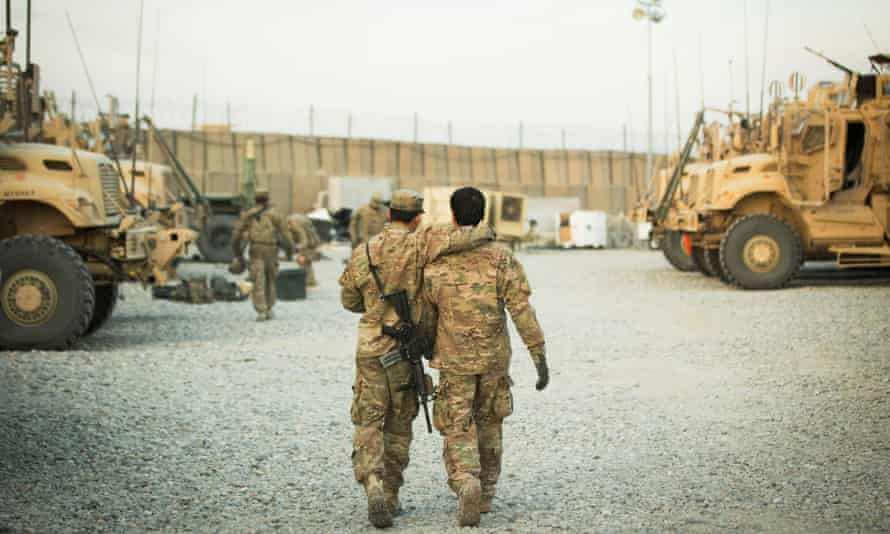 A US soldier from the 3rd Cavalry Regiment walks with the unit's Afghan interpreter before a mission near forward operating base Gamberi in the Laghman province of Afghanistan in December 2014