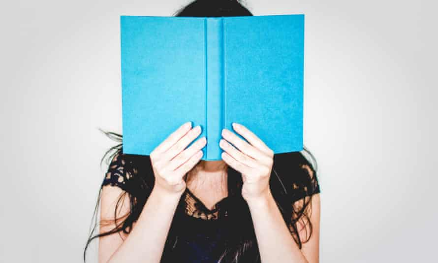 Woman hiding behind book