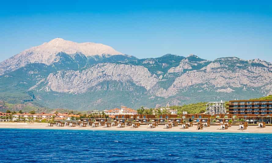 Hotel on the beach against the backdrop of the mountain Olympus (Tahtali Dagi), Turkey.