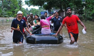 Volunteers and rescue personnel evacuate residents in a boat in Kozhikode, in the Indian state of Kerala.