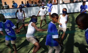 Partially blind boys play with sighted boys who have covered their eyes at a school in Maseru, Lesotho.