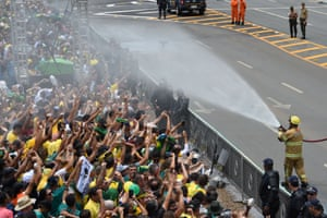 Firefighters spray water at supporters of the Brazilian president-elect Jair Bolsonaro