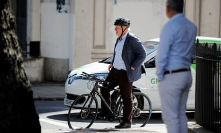 Conservative party leader Boris Johnson waits at a set of traffic lights on his bicycle in London.