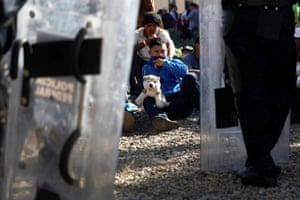 Edwin, 35, part of a caravan of thousands traveling from Central America en route to the United States, holds a stuffed dog as he takes part in a demonstration at the border wall between the US and Mexico in Tijuana