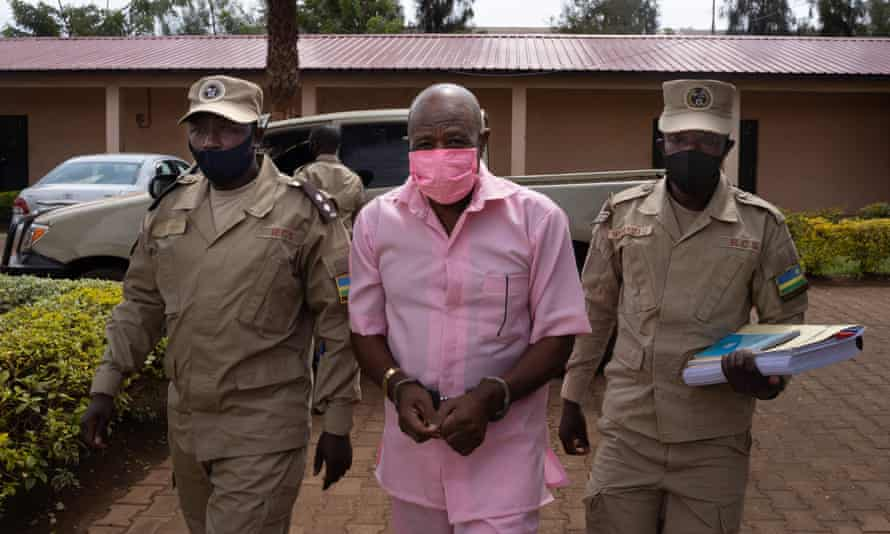 Paul Rusesabagina wears a pink prison inmate's uniform as he arrives at Nyarugenge Court of Justice in Kigali last October, flanked by guards.