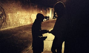 An exchange between a man and a woman on a dimly lit street.