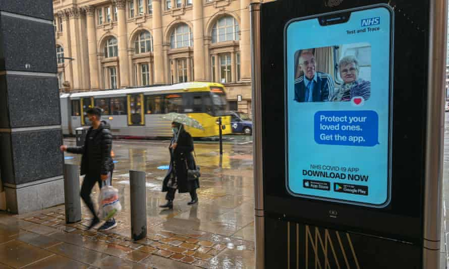 People in Manchester walk past an electronic sign asking them to download the NHS test and trace app