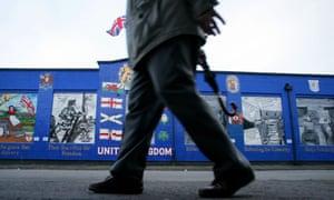 A man walks pass a Loyalist mural.