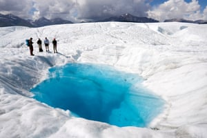 Hikers stand beside a pool on Root glacier at Wrangell-St Elias national park