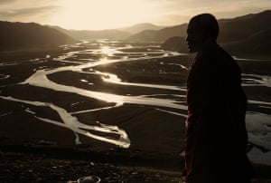 A Tibetan monk looks out onto the Yellow River.