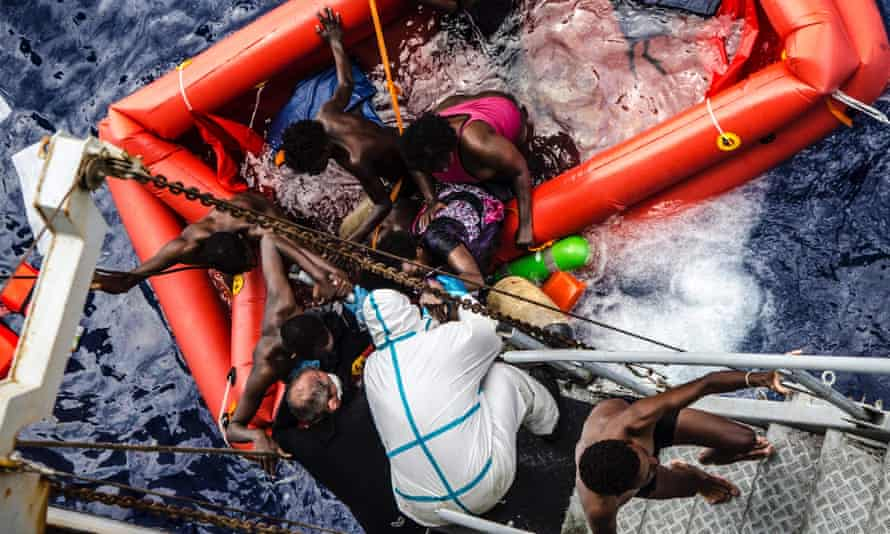 Rescuers help migrants to board the Italian Navy ship Vega, after the boat their boat sunk.