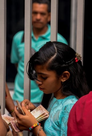 A girl counts 100-Bolivar-bills while people queue outside a bank in Caracas in an attempt to deposit money.