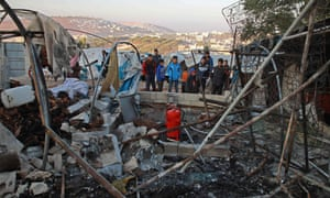 Civilians inspecting damage at camp in Qah