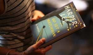 A man holding a copy of Harper Lee's Go Set A Watchman