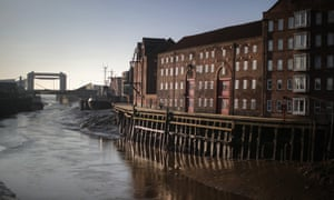 Converted former warehouses along the River Hull, with the tidal barrier in the distance.