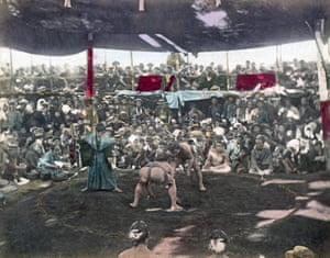 A hand coloured photograph showing a Sumo wrestling match in Japan circa 1880s.