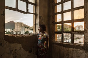 A woman stands at the windows of the abandoned Ministry of Finance building in the Mangueira favela in the North Zone in Rio de Janeiro. Women are often the chief breadwinners in their homes, the caretakers of the children and the elderly, and are frequently involved in efforts to improve their communities