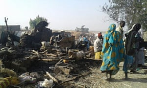 People stand next to site of bombing in Rann, northeast Nigeria