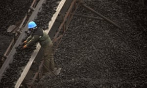 A worker monitors coal being carried along conveyor ramps at a coalmine in northern China.