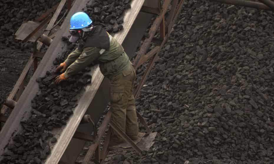 A worker monitors coal being carried along conveyor ramps at a coalmine near Ordos in northern China's Inner Mongolia autonomous region.