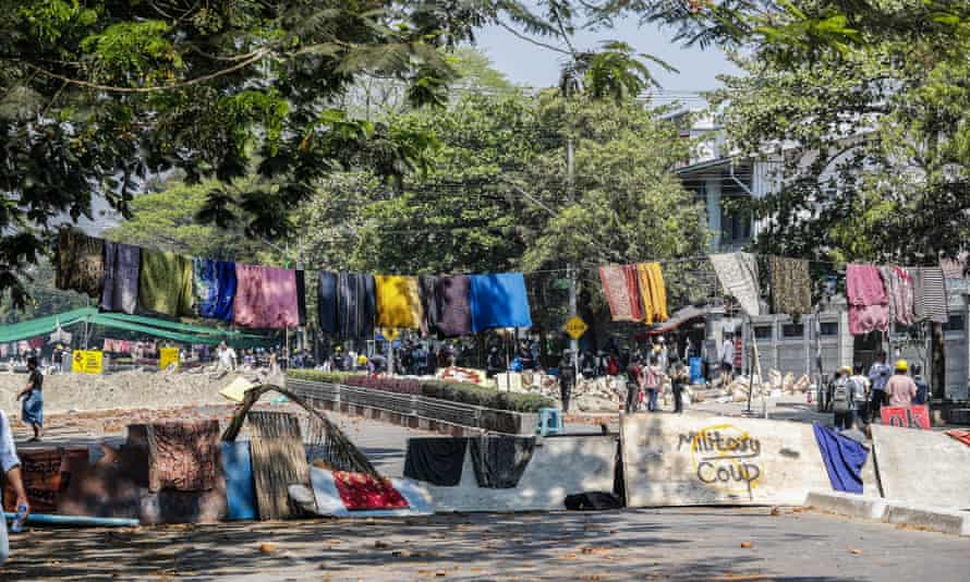 Protesters barricade a Yangon road with women's longyi.
