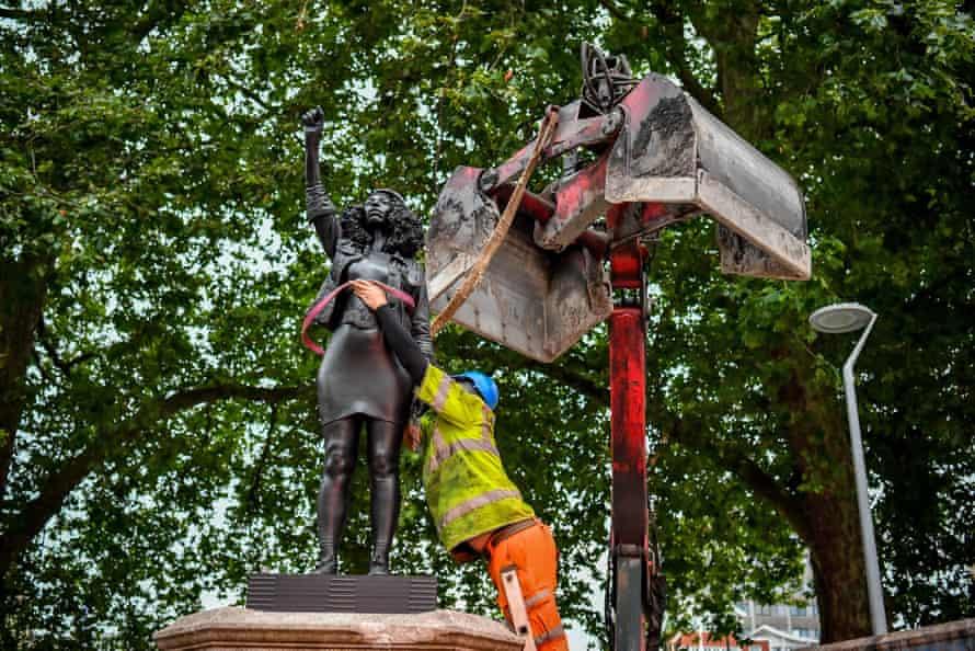 Contractors secure the statue.