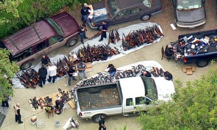 Police inspect a large cache of weapons seized at a home in the affluent Holmby Hills neighborhood of Los Angeles.