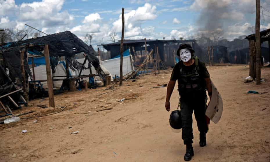 A police officer sports a Guy Fawkes mask he confiscated during continued government raids on illegal wildcat gold mining operations in La Pampa in 2016.