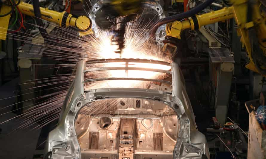 Robotic arms assemble and weld the body shell of a Nissan car on the production line at Nissan's Sunderland plant. The IMF predicts UK growth will slow next year.
