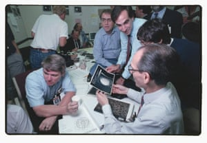 Voyager 2 scientists Carl Sagan (top C, in blue shirt and glasses) and Ed Stone (lower R) look at images captured of Neptune's moon Triton