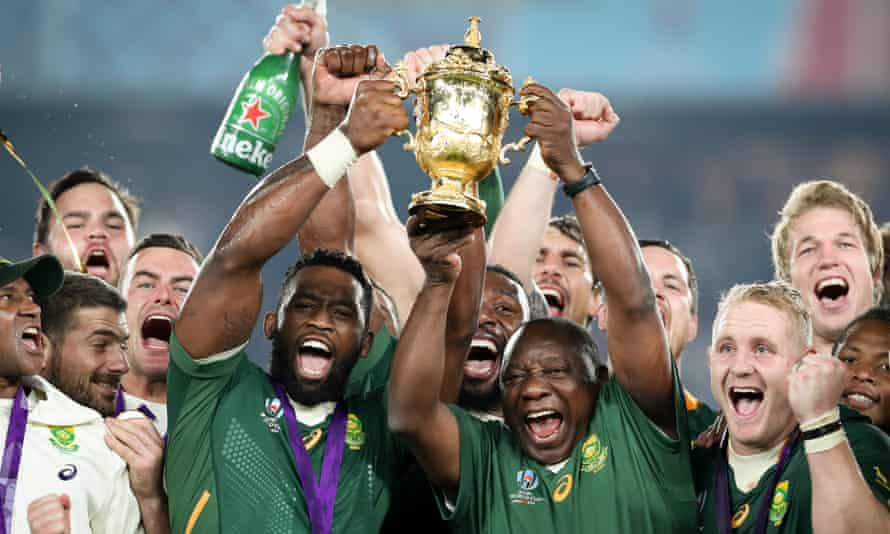 South Africa's captain Siya Kolisi and the country's president Cyril Ramaphosa hold the Webb Ellis Cup aloft.