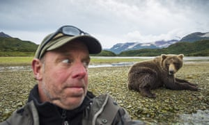 The American photographer Paul Souders takes a selfie with a grizzly bear near a salmon spawning stream in Katmai National Park, Alaska.